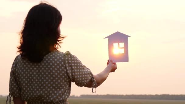 Silhouette eines Papierhauses. eine Frau träumt, hält ein Papierhaus in der Hand und schaut in den Sonnenuntergang.
