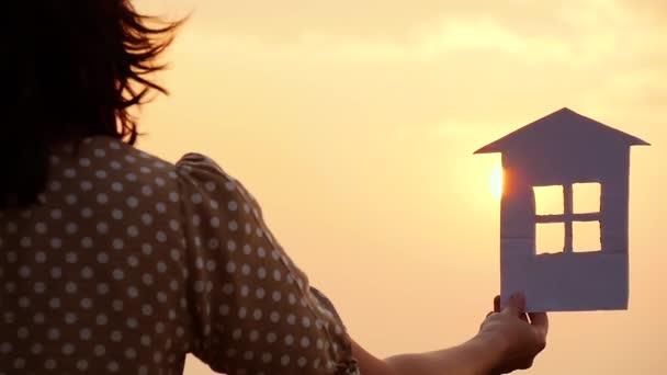 Hand hält ein Papierhaumodell gegen den Sonnenuntergang. Familienkonzept, Bau- und Immobilientransaktionen.