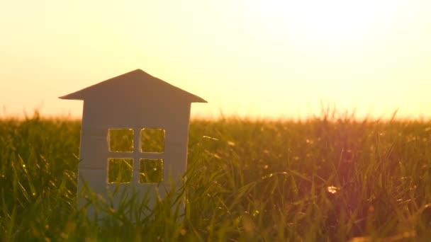 Dům z papíru stojí proti zelené trávě. Okny procházejí sluneční paprsky. c