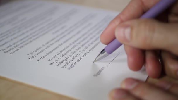 Der Mann unterschreibt das Vertragsdokument in Großaufnahme.
