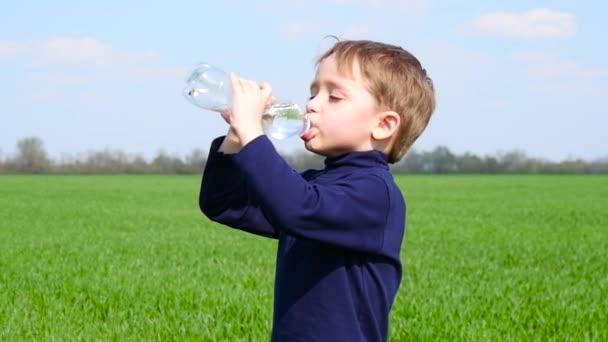 Malý chlapec uhasí žízeň vodou z plastové láhve. Dítě pije vodu v přírodě za slunečného dne.