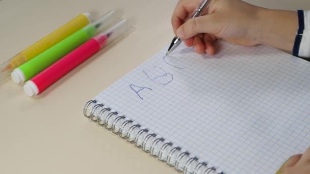 Ruce malého dítěte zblízka. Dítě studuje dopisy a píše je perem na bílý papír u stolu.