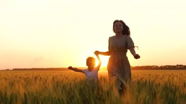 A happy mother holds her childs hand and runs across a wheat field at sunset. A mother and a little boy run through the golden wheat.