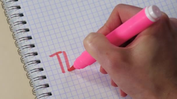 A womans hand writes the word THANK YOU with a pink marker in a Notepad.