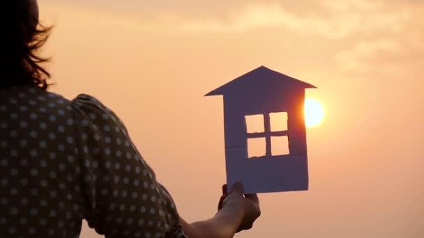 Papierhausmodell als Symbol einer glücklichen Familie, Träume von der Zukunft. Silhouette eines Hauses bei Sonnenuntergang in der Hand.