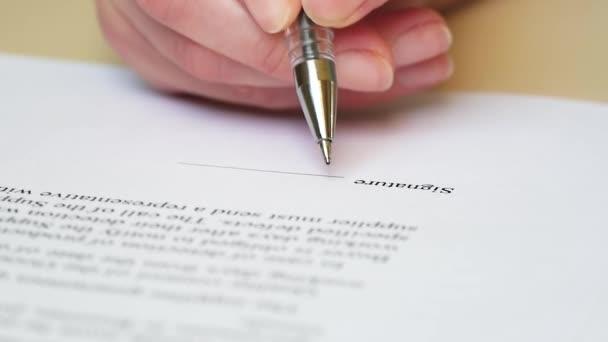Hand hält einen Füllfederhalter in Großaufnahme. ein Unternehmer unterschreibt einen Vertrag. abstrakter Text eines Geschäftsdokuments.