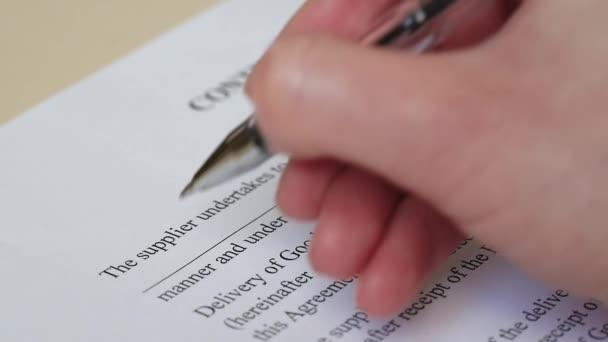 Hand hält einen Füllfederhalter in Großaufnahme. ein Unternehmer gibt das Wort Organisation in den abstrakten Text eines Geschäftsdokuments ein.