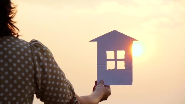 The girl holds a model of a paper house in her hand. The rays of the sun during sunset pass through the window of the paper house. The concept of building a happy family. Silhouette.