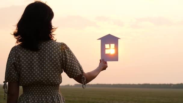 Dívka drží v ruce model papírenského domu. Paprsky slunce při západu slunce procházejí oknem papírenského domu. Koncept budování šťastné rodiny.