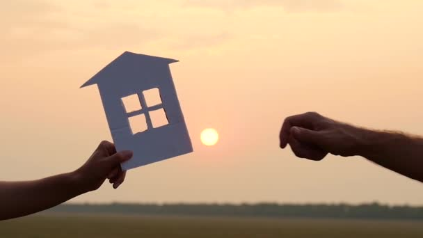 A man and a woman pass each other a model of a paper house on the background of the sunset. Concept of real estate transactions, construction and families.