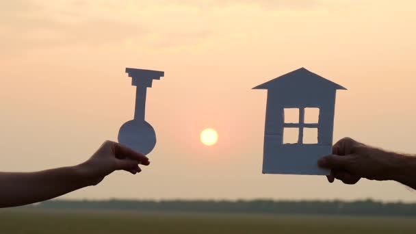 Silhouette of a paper house model at sunset. A man and a woman hold a paper house and a key against the background of the sunset.