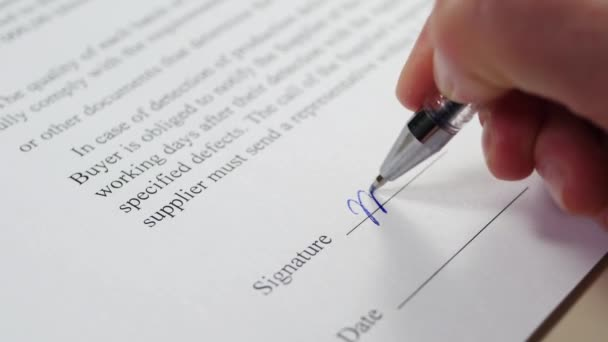 The hand of a business person signs a document, a contract. The concept of business transactions.