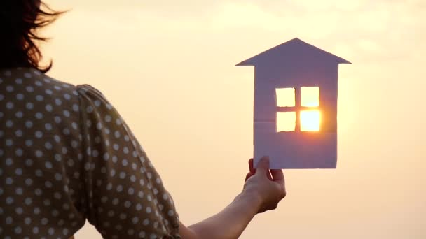 Silhouette of a girl holding a model of a paper house in her hand. The rays of the sun during sunset pass through the window of the paper house. The concept of building a dream of a happy family