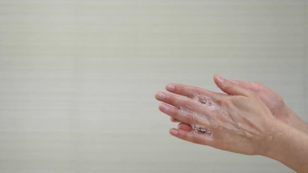 Egy nő fehér szappanbuborékokkal mossa a kezét közelről. Kézmosás bemutatása a vírusok elleni védelem érdekében. A higiénia és a megelőzés fogalma coronavirus