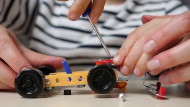 Detailní záběr rukou dítěte a ženy. Matka a syn hrají sestavením automobilového modelu od konstruktéra, utažením šroubů a matic šroubovákem. Šťastná rodina. Spolupráce, vývoj