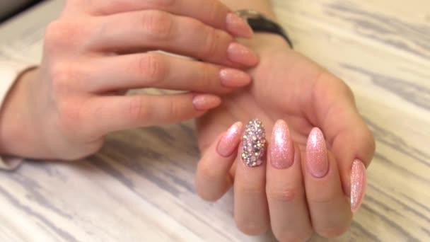 Nageldesign. Hände mit natürlicher Maniküre auf hellem Hintergrund. Nahaufnahme weiblicher Hände mit trendigen Dekorationen.mit rosa Nahsicht, Zeitlupe