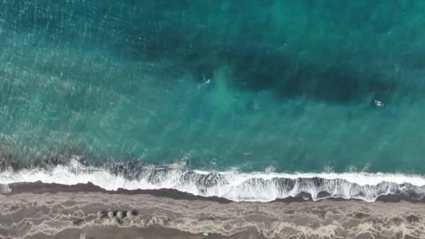 Pláž s slunečníky a lehátky na břehu tyrkysového moře, Řecko Santorini