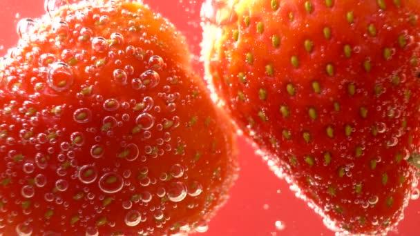 Červená jahoda krásně do vody s bublinkami.