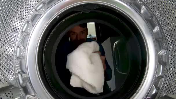Ember tesz törölközőt a mosógépbe