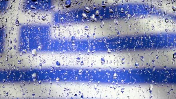 sok csepp víz az ablaküvegen heves esőzés idején. Közelkép Görögország integető zászló