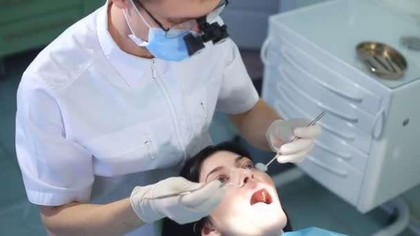 The dentist begins to examine the oral cavity of a beautiful girl