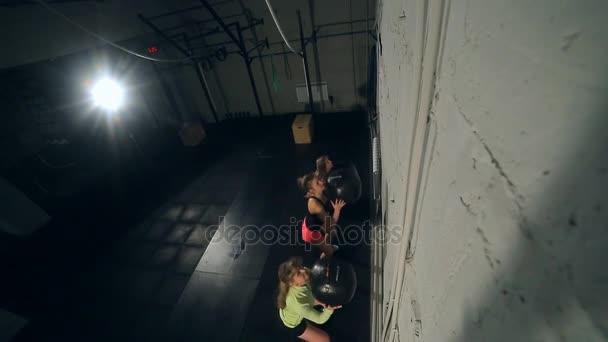 Tři krásné svalnaté fit dívky s cross fit ball, sexy mini šortky
