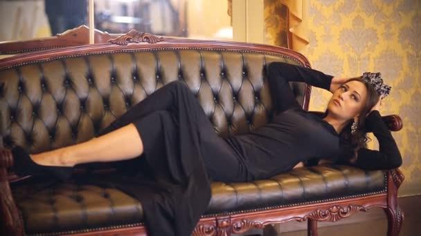 Gyönyörű lány szexi hosszú ruha, smink és egy fotós egy klasszikus belső jelentő korona