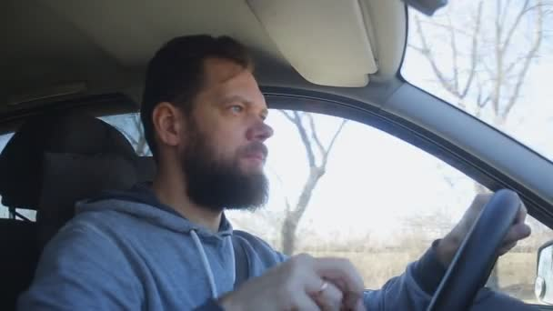 A man with a beard rides in the car and puts on sunglasses