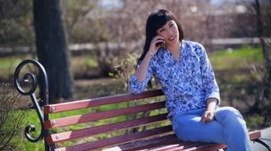 Beautiful Asian girl sitting in a park on a bench in blue jeans and talking  on