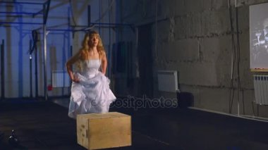 Beautiful and muscular blonde bride in a wedding dress jumping into wooden boxes in a training. Crossfit