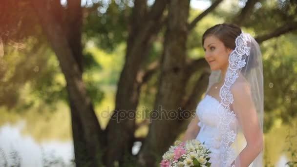 Gyönyörű menyasszony áll közel a tó és a vár, a vőlegény