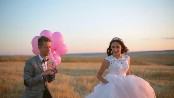 Nevěsta a ženich v oboru při západu slunce s balónem