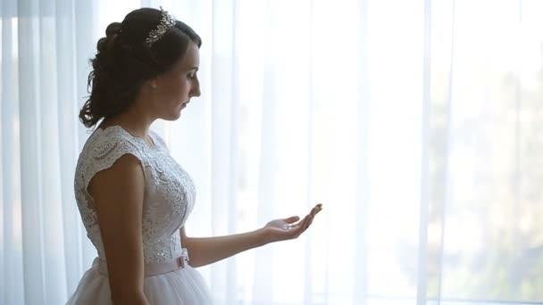 gyönyörű menyasszony, a vőlegény vár és a gazdaság a fülbevaló, a tenyerébe