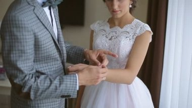 Groom helps put on a bride bracelet on hand at the wedding day in the hotel room