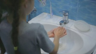 Little girl washing her hands in the bathroom
