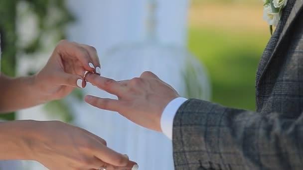 Nevěsta a ženich vyměnit snubní prsteny na pozadí zelené přírody. Ženich dává prsten na rameni jeho nevěsta detail. Svatební den.