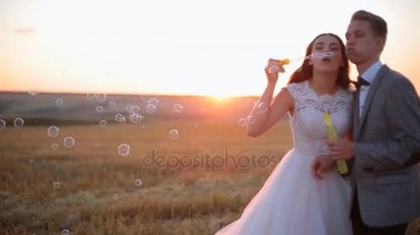 beautiful bride and groom laugh and blow soap bubbles in the park at sunset