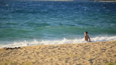 a man enters the water, the Mediterranean, Greece. Travel, summer vacation on the beach.