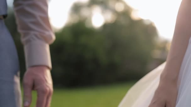 A Romantic Bride and Groom Couple Holding Hands on Wedding Day at Sunset.
