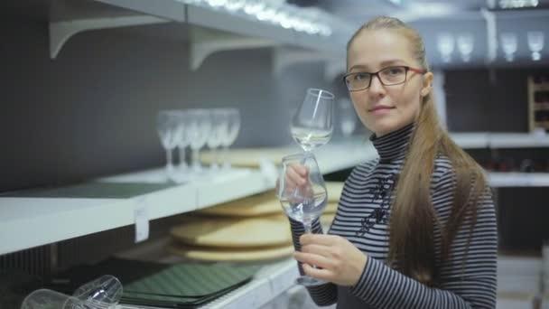 Evropská dívka s brýlemi zvolí sklenky na víno v obchodě