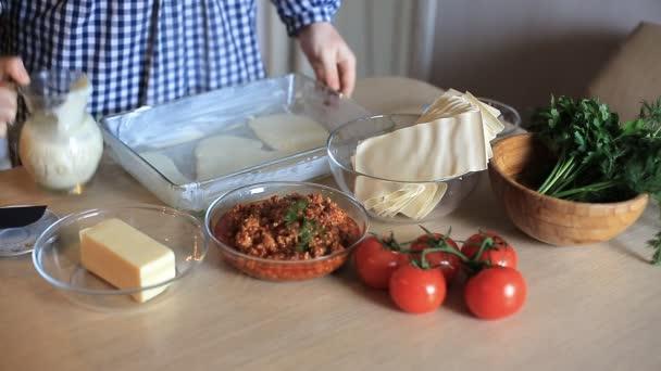 Hospodyně vaří maso lasagne v kuchyni. domácí potraviny