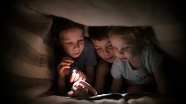 Two sisters and a brother read a book under a blanket with a two sisters and a brother read a book under a blanket with a flashlight in a sciox Gallery