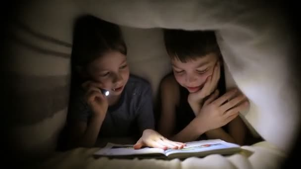 Brother and sister read a book under a blanket with a flashlight in brother sciox Gallery