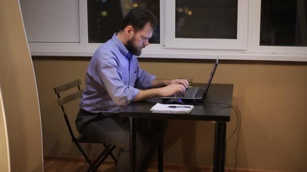 unavený podnikatel pracuje v podvečer s přenosným počítačem v kanceláři a skládá finanční zpráva.