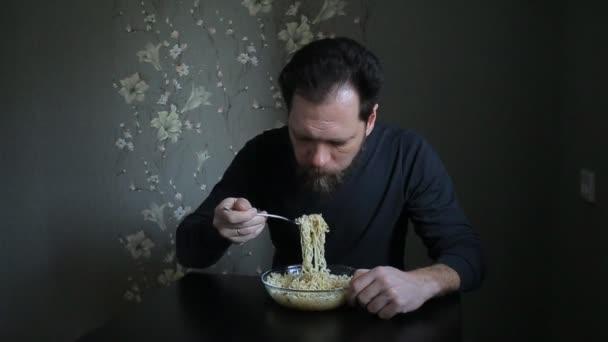 vousatý muž jíst instantní nudle