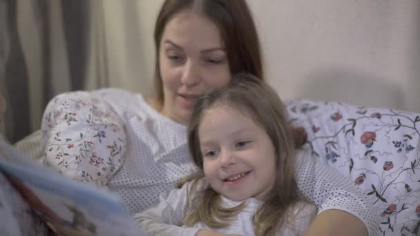 mom reads fairy tale to little daughter in bed before going to bed.