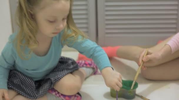 két lány festék akvarell festékek és ecsetek egy nagy rajz papír a padlón, gyerekek közös kreativitás.