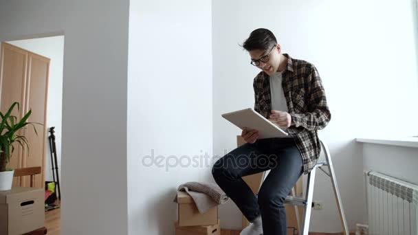 Člověk s použitím tabletu v novostavbě domu po přestěhování