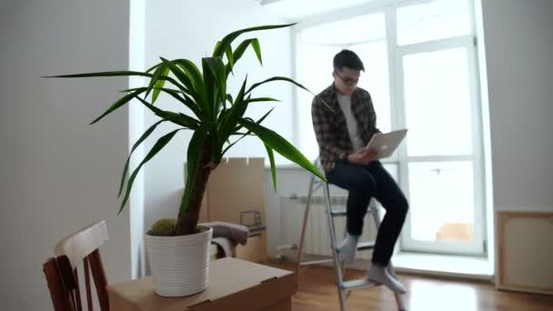Glimlachend jongeman op zoek naar sommige decoratie ideeën op een
