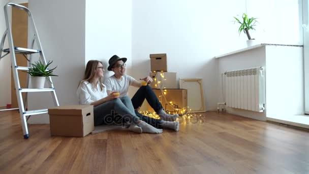 Mladý pár sedí na podlaze
